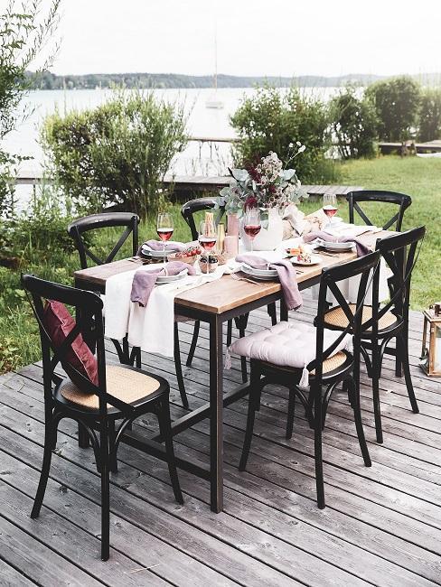 terras met houten tafel met zwarte stoelen