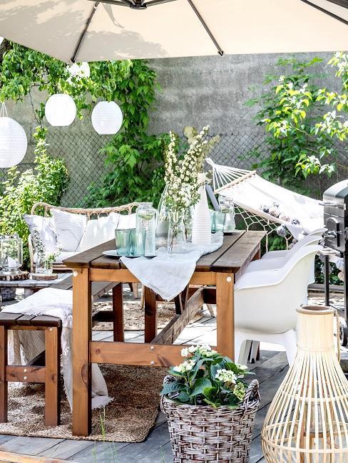 houten tafel met houten bank met witte stoelen