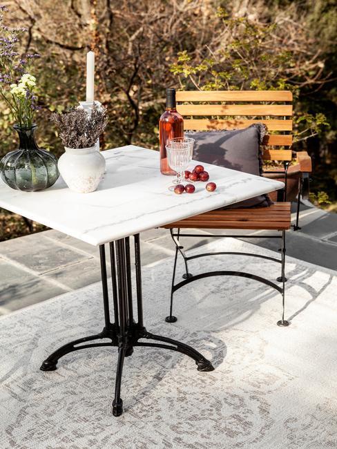 houten stoel met grijs kussen en een witte marmeren tafel