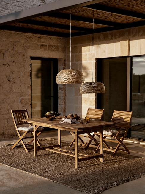 houten tuinset met rieten buitenkleed en lamp