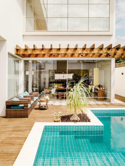 houten veranda met houten stoelen en blauw zwembad