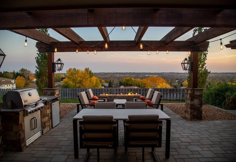 donkergrijze stoelen met bbq en veranda van hout