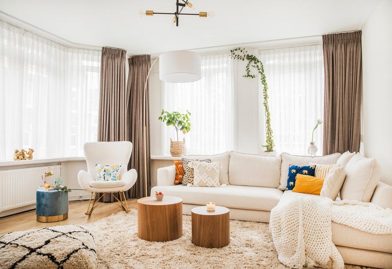 woonkamer met witte bank en witte stoel met gouden poten