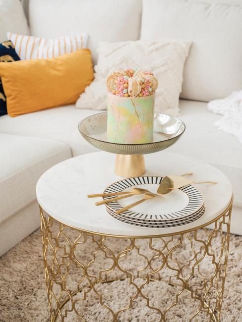 marmere tafel met gouden poten en gele kussens