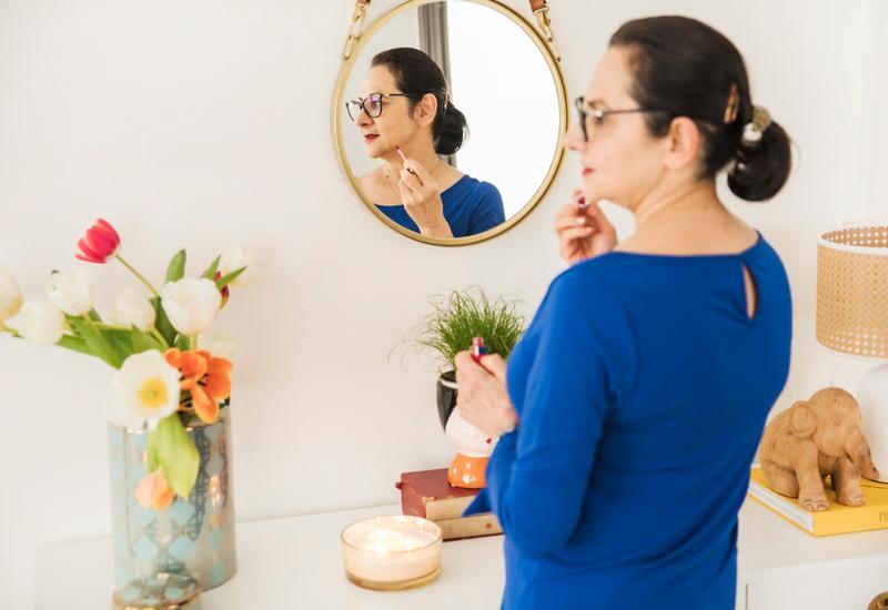 vrouw in een blauwe jurk voor een goude ronde spiegel
