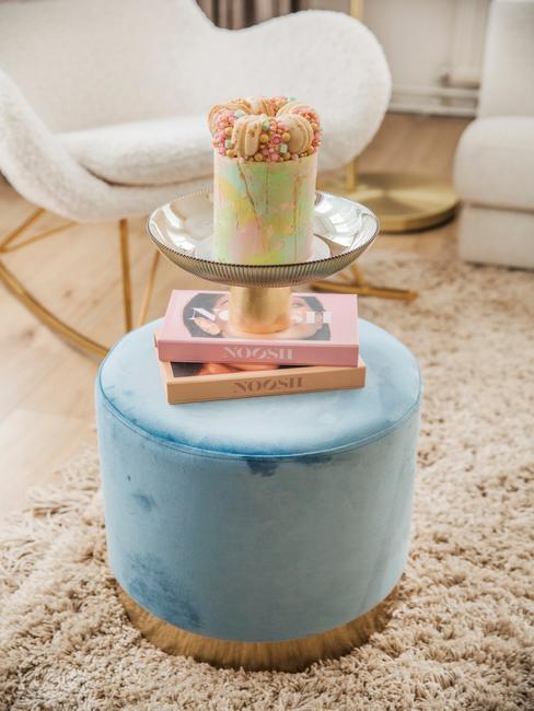 blauwe poef met goude poten en roze boeken
