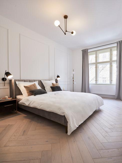 grijze boxspring met zwarte lampen op een houten vloer