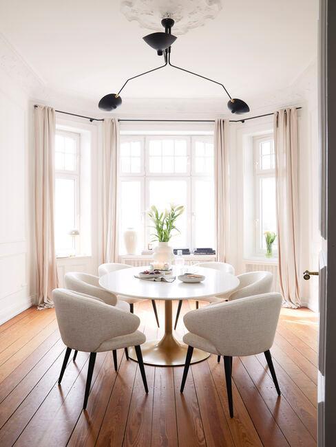 ovale tafel met grijze stoelen en zwarte plafondlamp op een houtenvloer