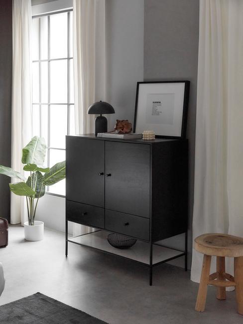 zwarte kast met zwarte lamp en houten kruk