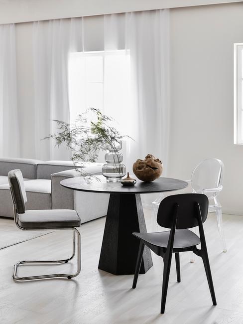 zwarte ronde tafel met zwarte en grijze stoelen op een lichte vloer