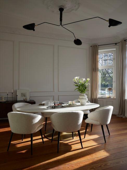 houten vloer met ovale tafel en grijze stoelen en zwarte hanglamp