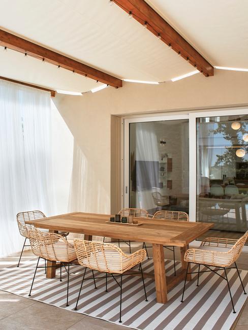 veranda met een houten tafel met rieten stoelen en outdoor kleed