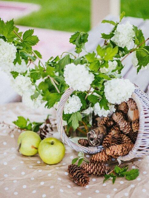 decoratie sneeuwbal bloemen in rieten mand met appels en dennenappels