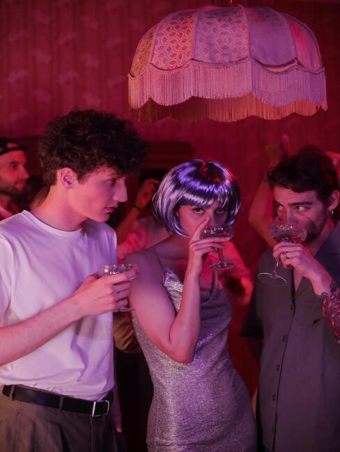 twee mannen met vrouw met een paarse pruik