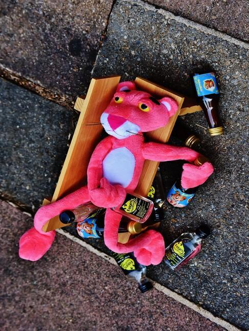 pink panter knuffel op straat met drank flesjes