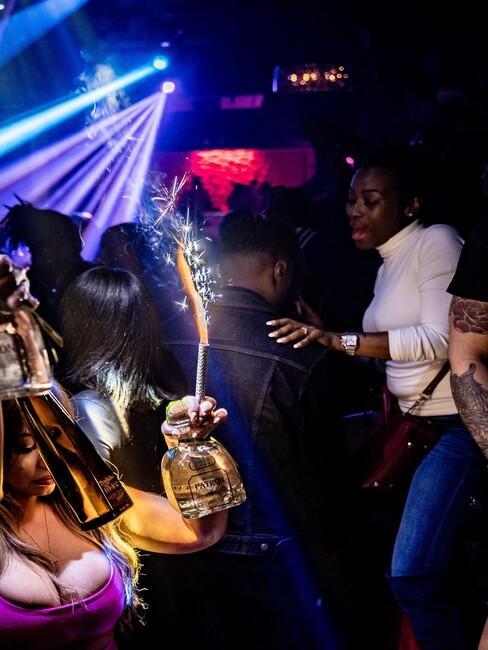 mannen en vrouwen in de club met drank en vuurwerk