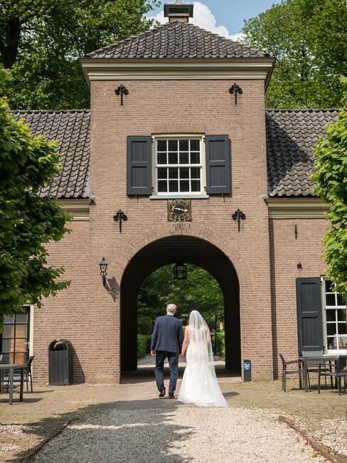 bruid en bruidegom lopen door een oude poort