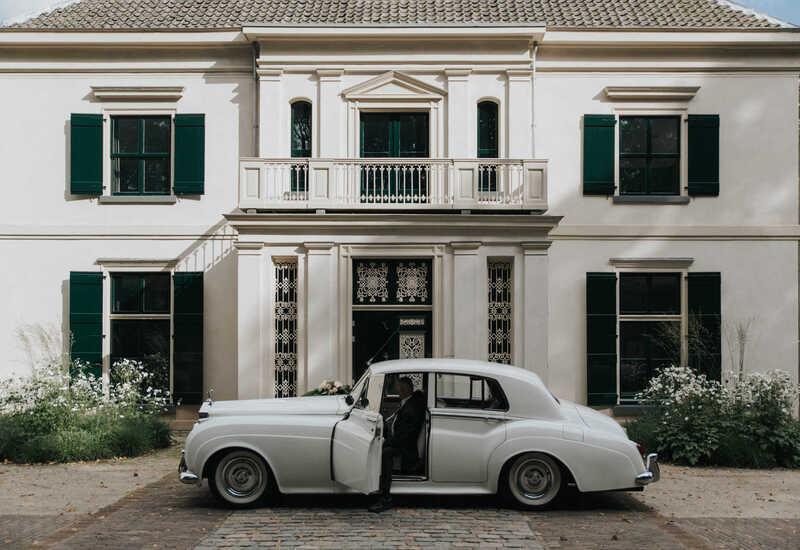 wit landgoed met oude witte auto ervoor