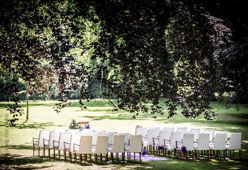 witte stoelen op het gras met grote bomen