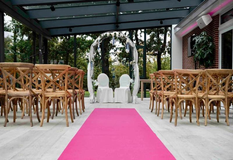 roze loper naar het altaar met houten stoelen