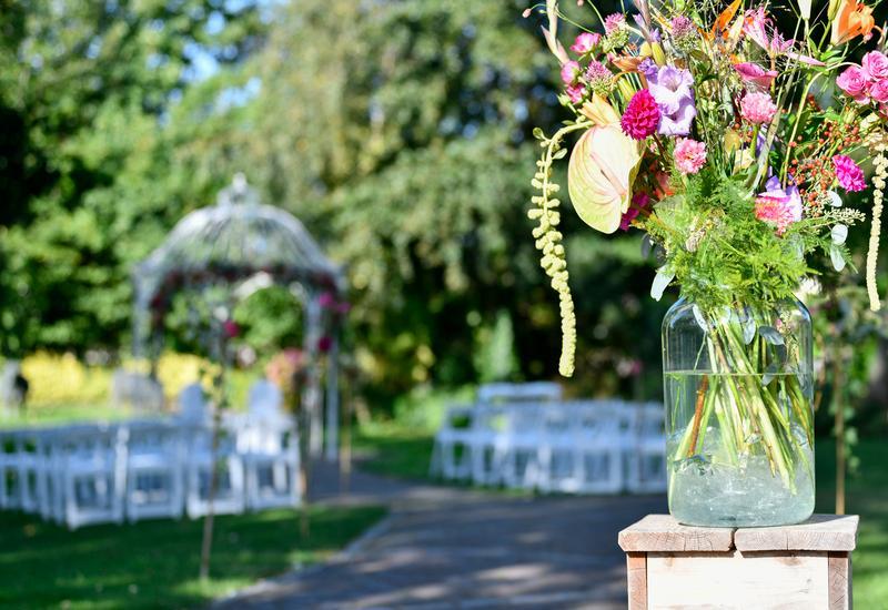 witte stoelen en een vaas met veldbloemen