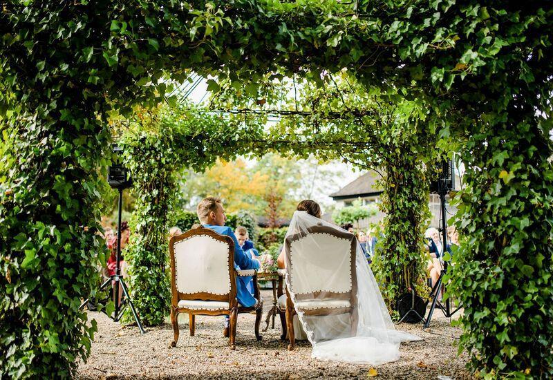 witte stoelen in een bomen boog met bruid en bruidegom