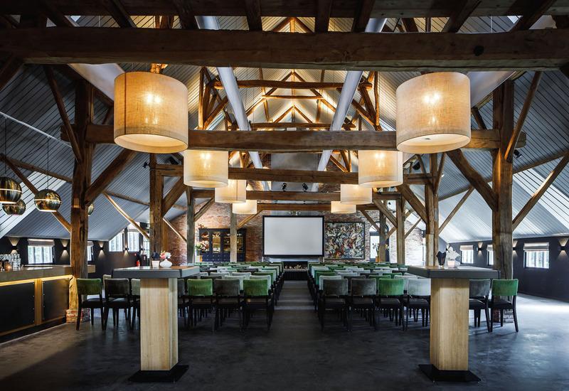 zaal met groene stoelen en witte lampen