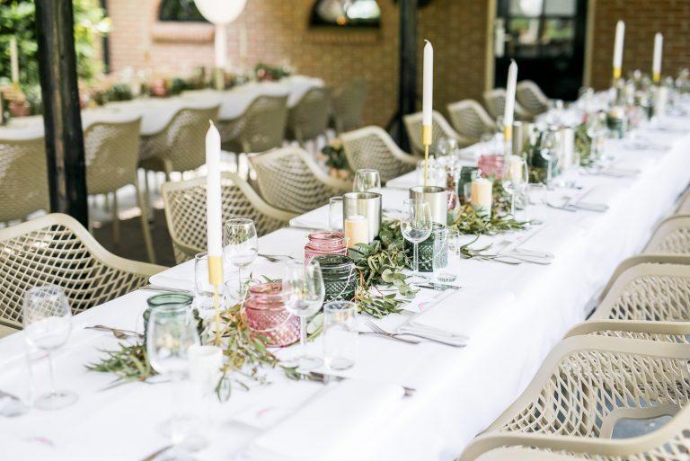 wit gedekte tafel met hoge kaarsen en toupe stoelen