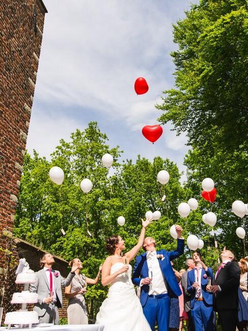 bruid en bruidegom voor landgoed met witte en rode ballonnen