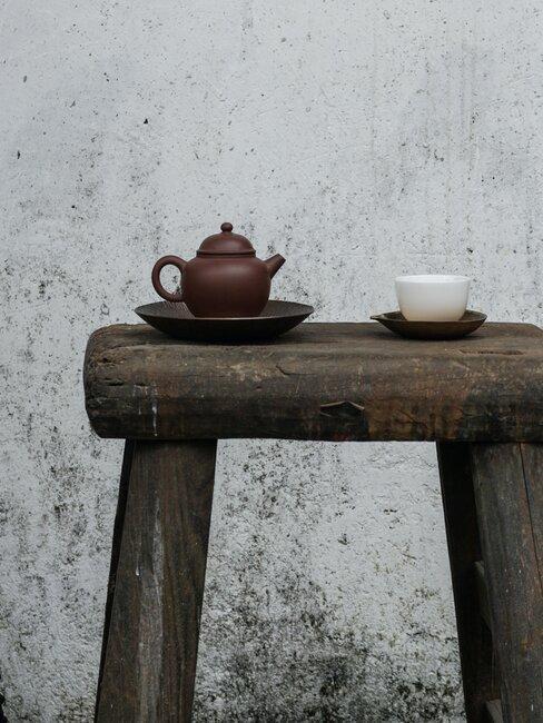 theepot met theekopje op een houten tafeltje