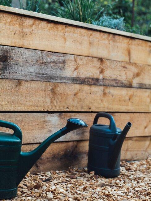 twee gieters en een houten schutting
