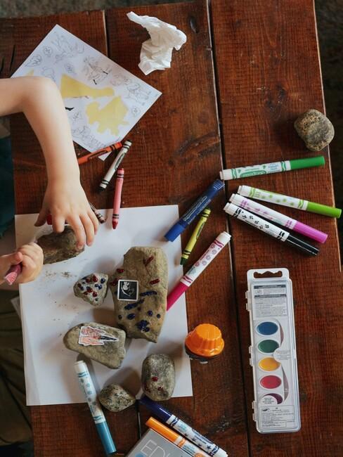 kind dat aan het knutselen is met gekleurde stiften