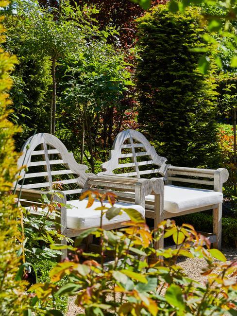 houten stoelen met witte kussens en groene beplanting voor een engelse tuin