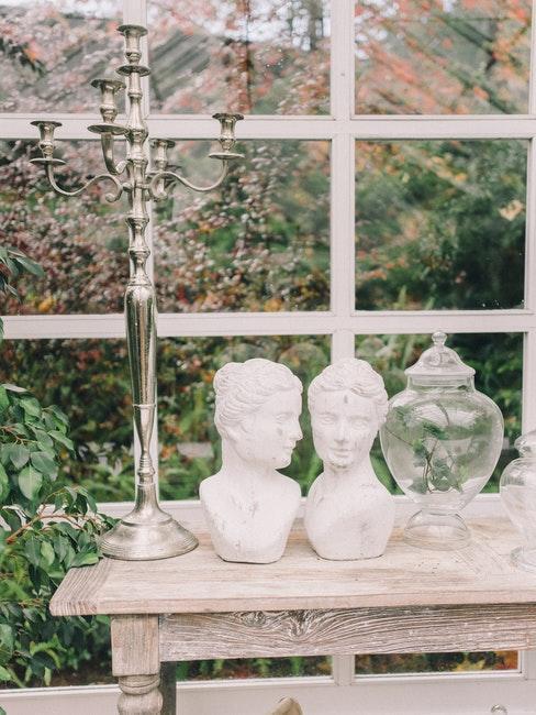 tafel met 2 witte beelden en een glazen vaas