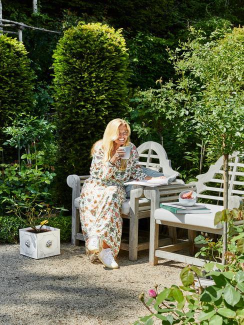 vrouw op een witte houten stoel in een landelijke tuin