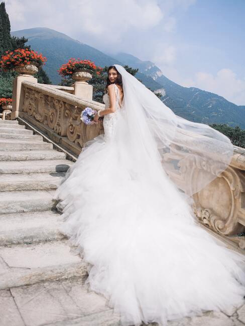 bruid op een trap met rode bloemen