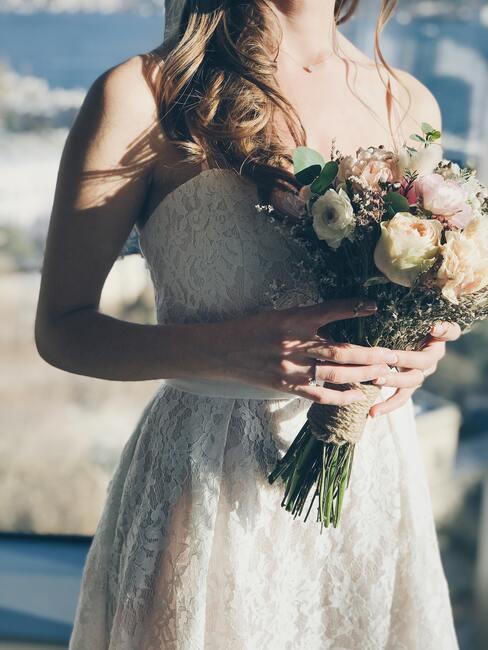 vrouw met bruidsjurk en wit met roze boeket
