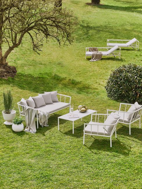 witte tuinmeubels met grijze kussens in een grote tuin