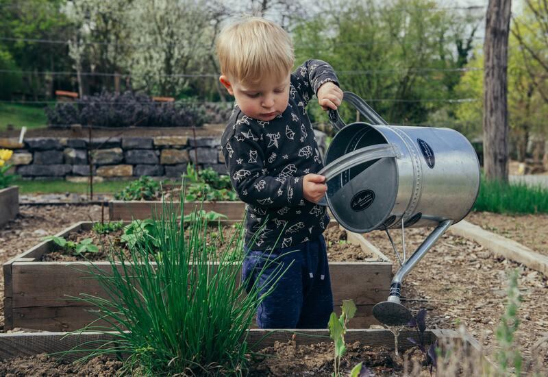 jongen die aan het tuinieren is in een kindvriendelijke tuin