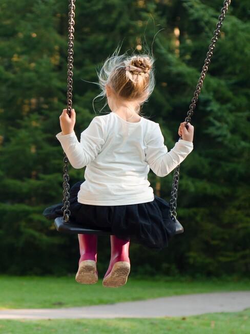 meisje op een schommel voor een kindvriendelijke tuin