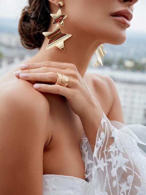 vrouw met gouden sterren oorbellen en witte trouwjurk