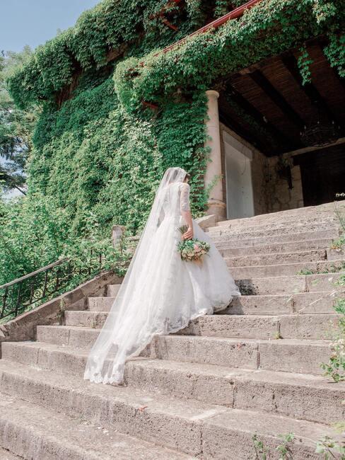 vrouw in een trouwjurk op een trap