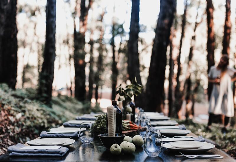 houten gedekte tafel met wit servies en zilver bestek