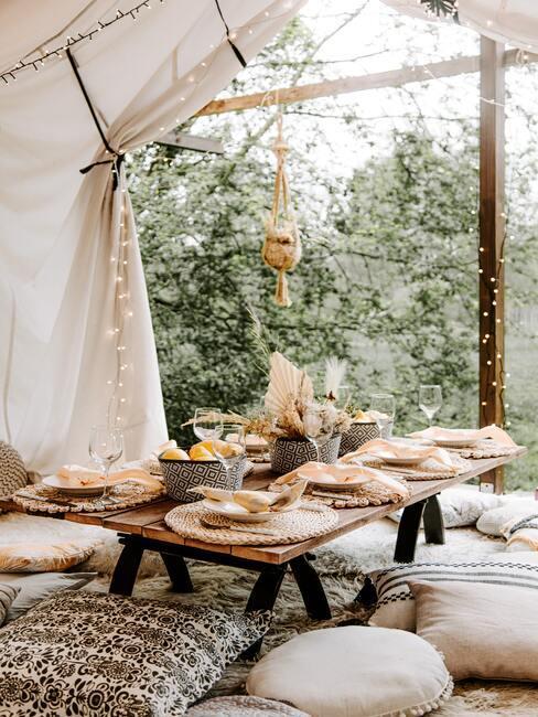 witte zitkussens met een houten gedekte tafel en lampjes in een tent