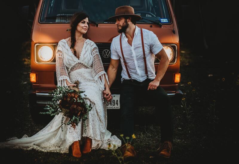 bruidspaar met bloemen met een gele bus
