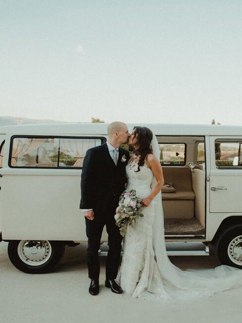 bruidspaar voor en witte bus
