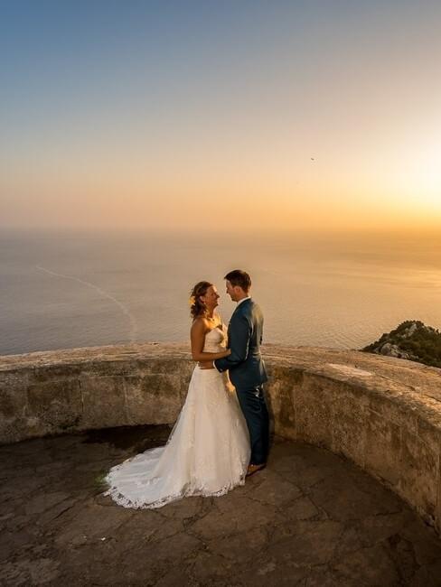 Trouwpaar aan de zee bij zonsondergang