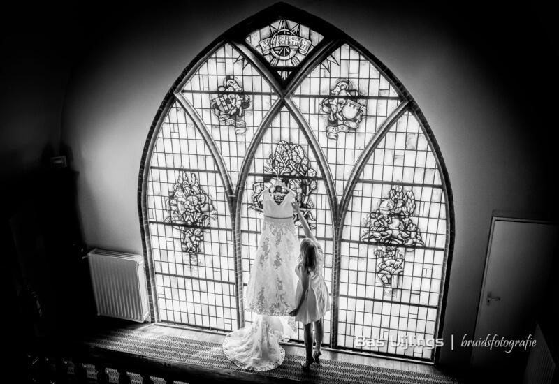 bruidsfoto in kerk voor glas in lood raam