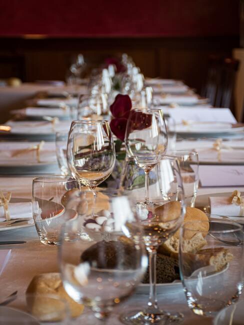 gedekte tafel met rode details en wijnglazen