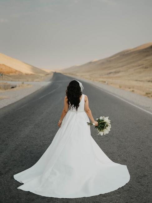 bruid met een witte bruidsjurk op een weg